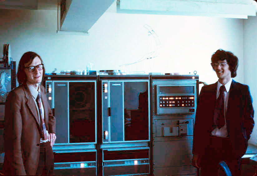 Two men in suits in the 1970s standing in front of a mainframe computer