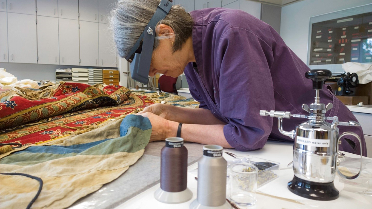A conservator leans over a piece of colorful fabric, examining it with a magnifying glass on a head mount