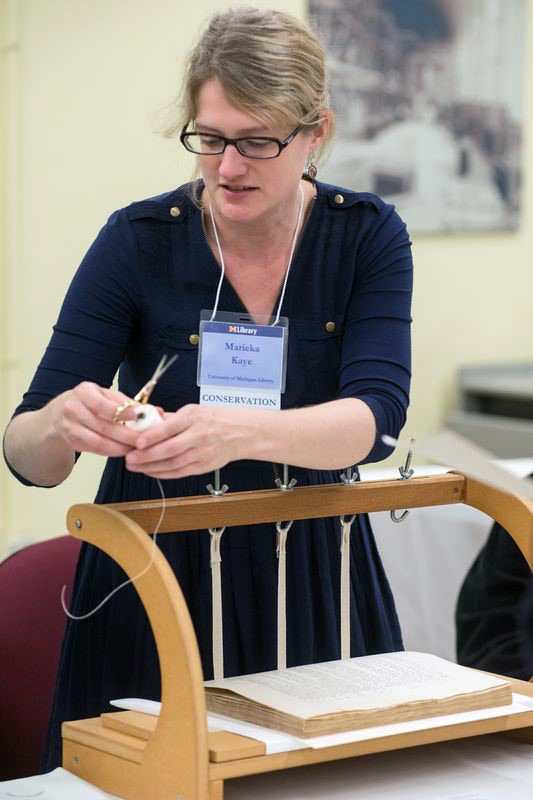 A blonde woman stands, working to restring the binding of a rare book