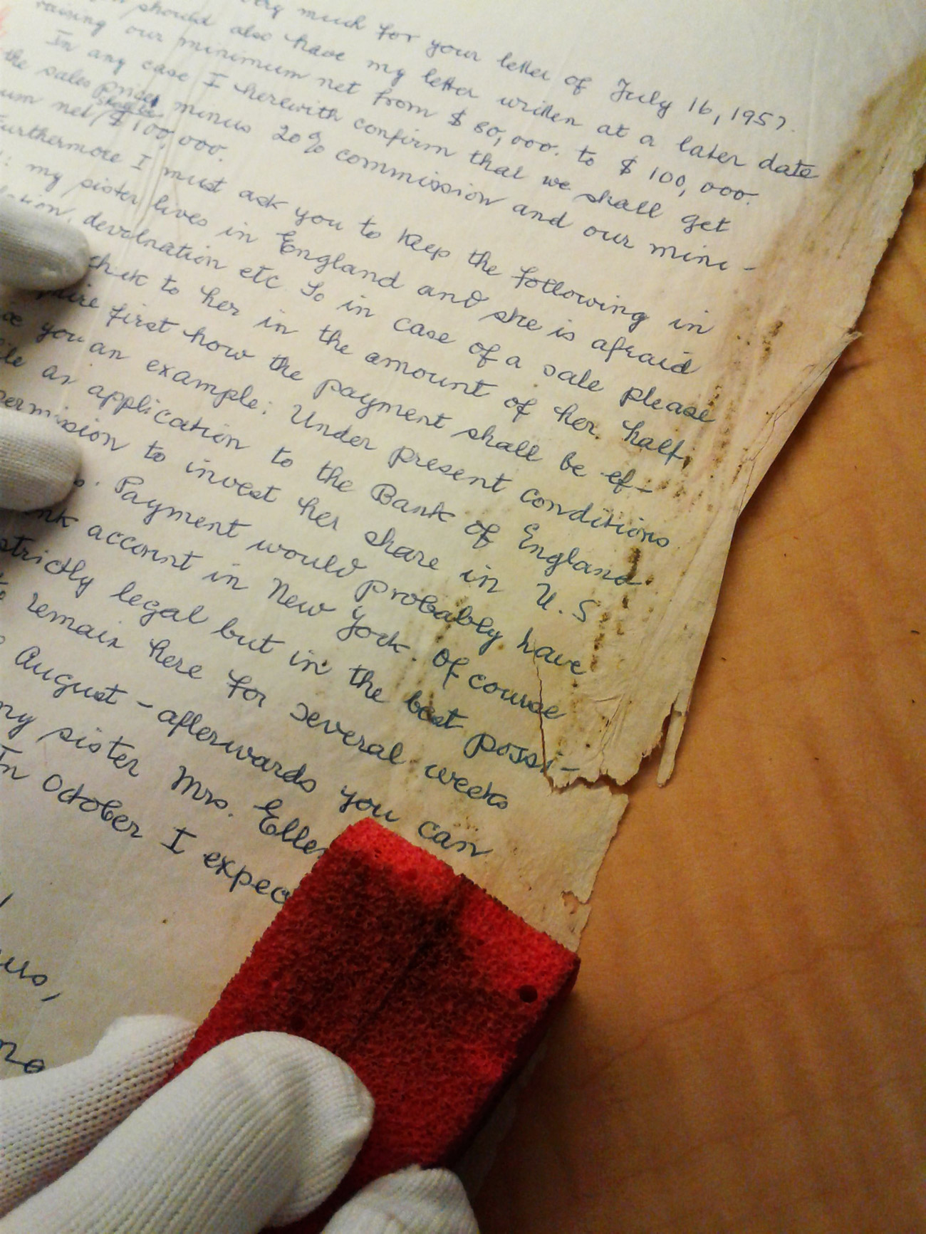 Using an absorene sponge to carefully clean mold off a letter from the M. Knoedler & Co. correspondence
