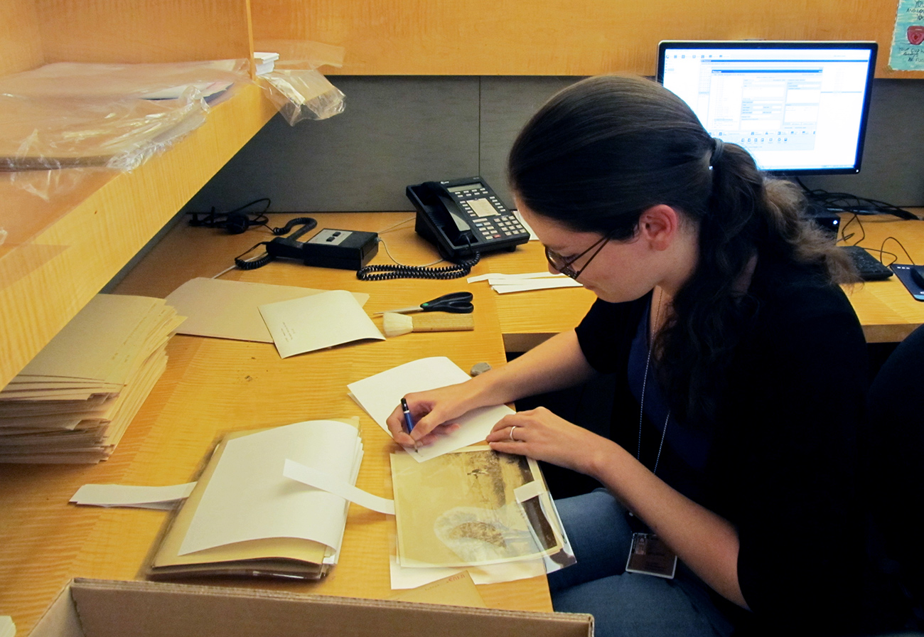 Sarah Glover, Getty Research Institute graduate intern in 2014–15, selects a photograph for digitization and sleeves it in Mylar.