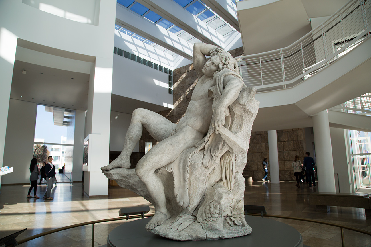 Over-life-size marble sculpture of a naked, reclining faun in the Getty Center's light-filled entry rotunda