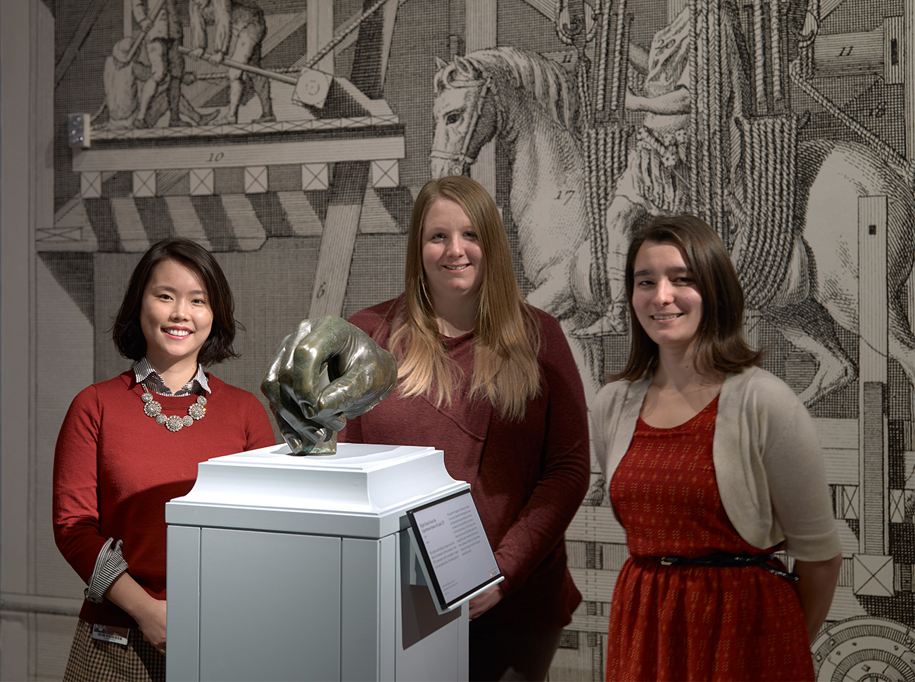 Three young women standing in a museum gallery behind an over-life-size bronze male hand on a pedestal