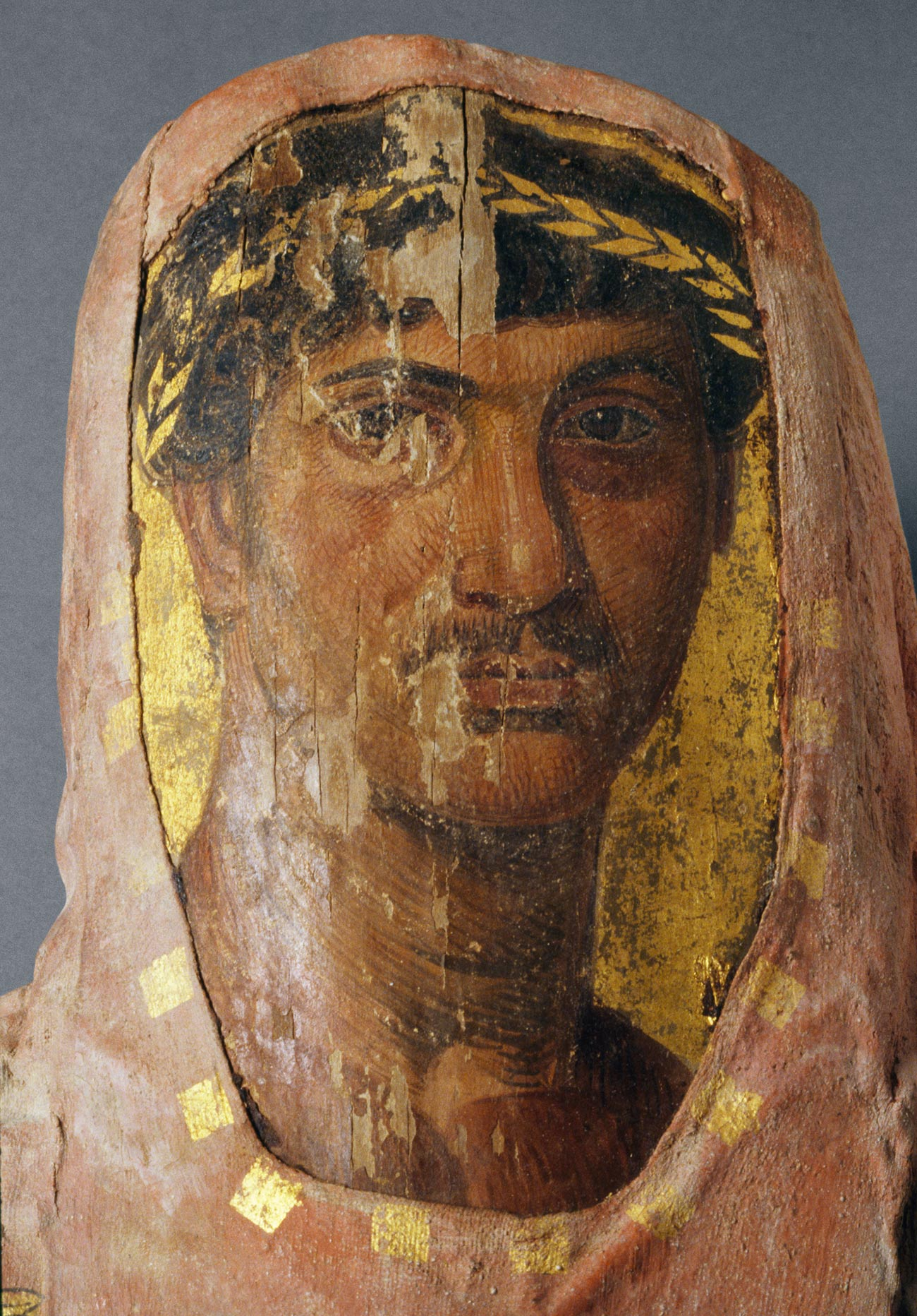 Close-up of encaustic-on-wood portrait of an ancient Egyptian with dark hair and a gold headband