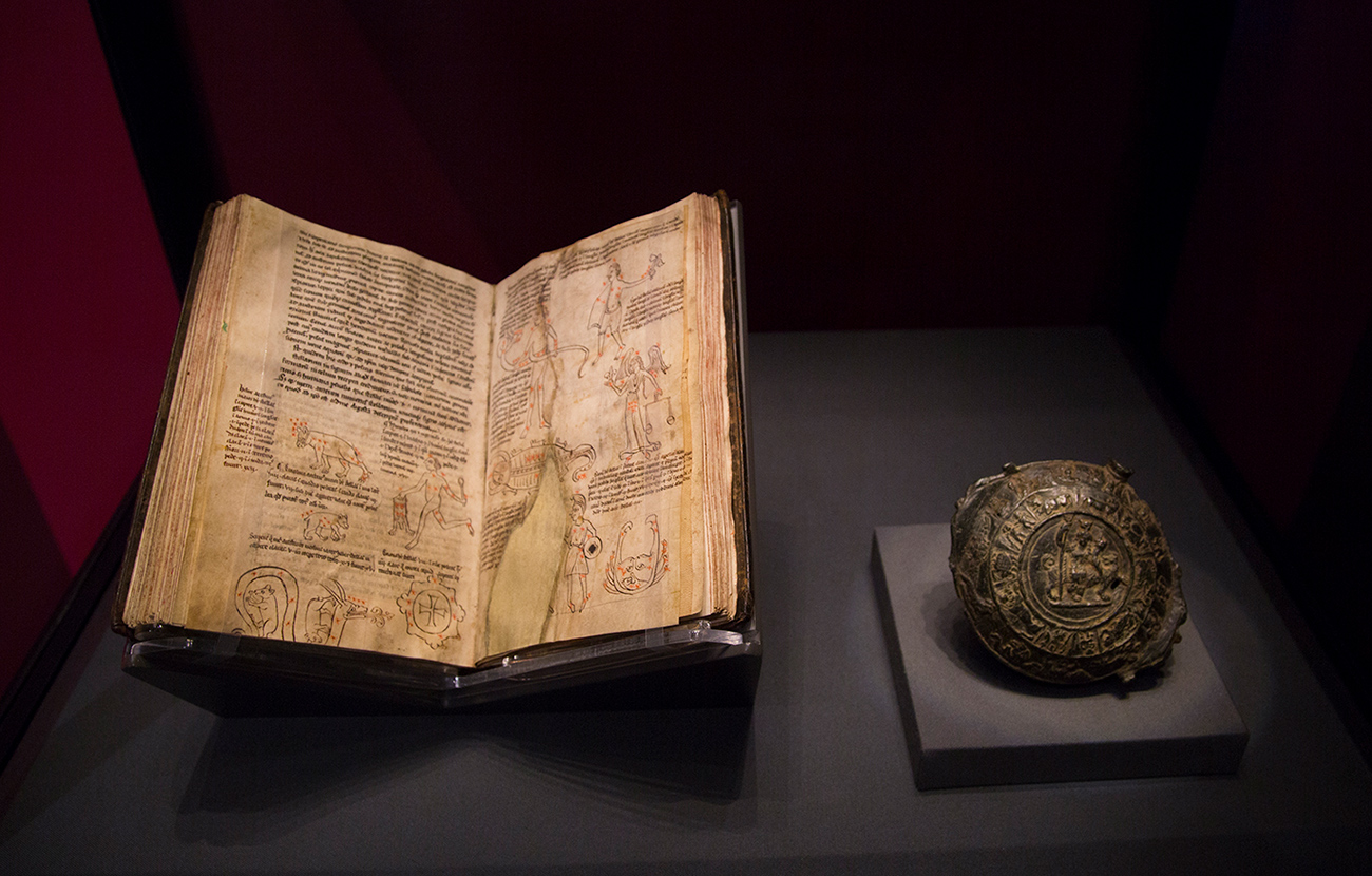 A medieval manuscript showing diagrams of the constellations in a display case next to an ancient Roman zodiacal medal