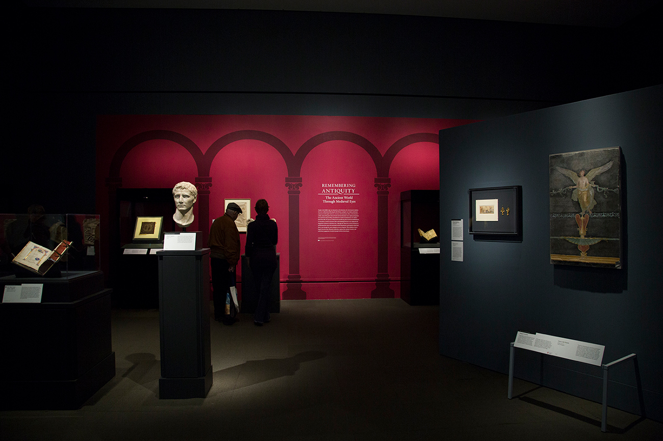 Gallery view of the exhibition Remembering Antiquity showing the red title wall with column motifs and several medieval manuscripts and Greek and Roman antiquities