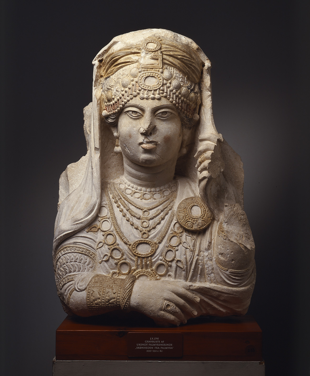 Limestone bust of an ancient Palmyrene woman wearing an elaborate headdress and seven necklaces