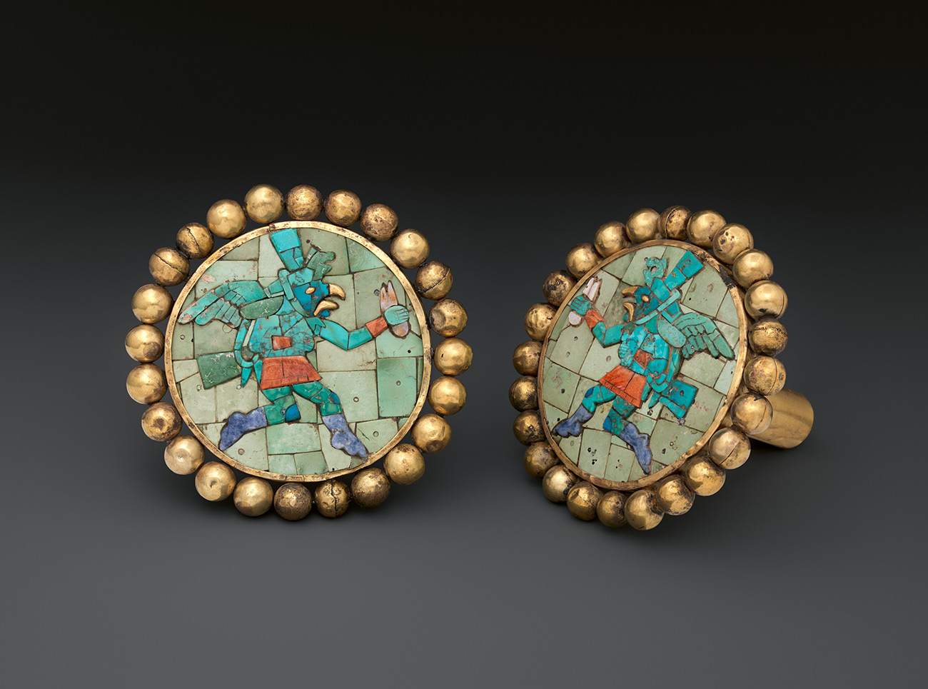 Pair of stone-and-gold ear ornaments in the shape of warriors