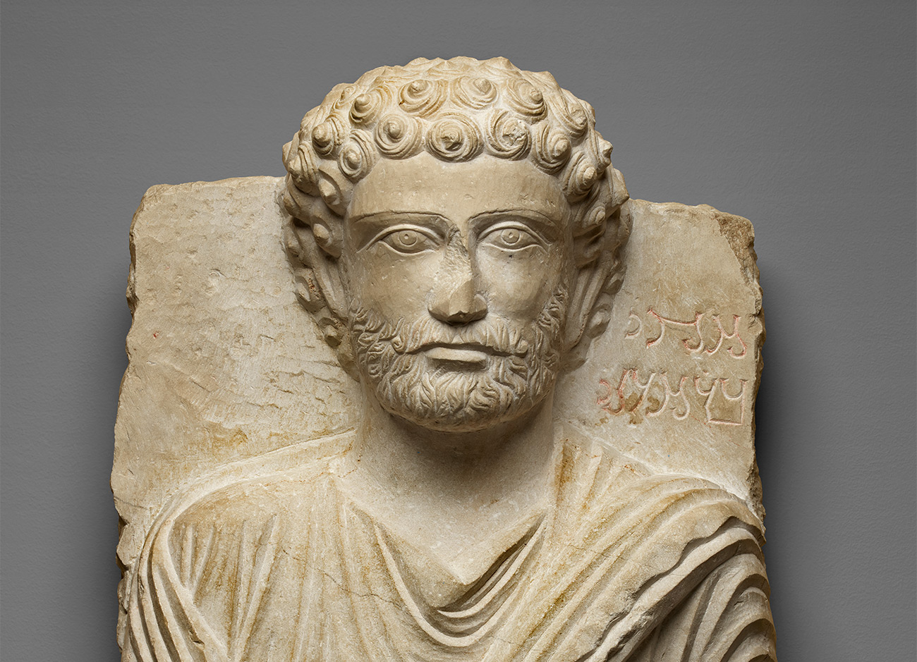 Limestone bust of an ancient Palmyran with snail curls and a tunic