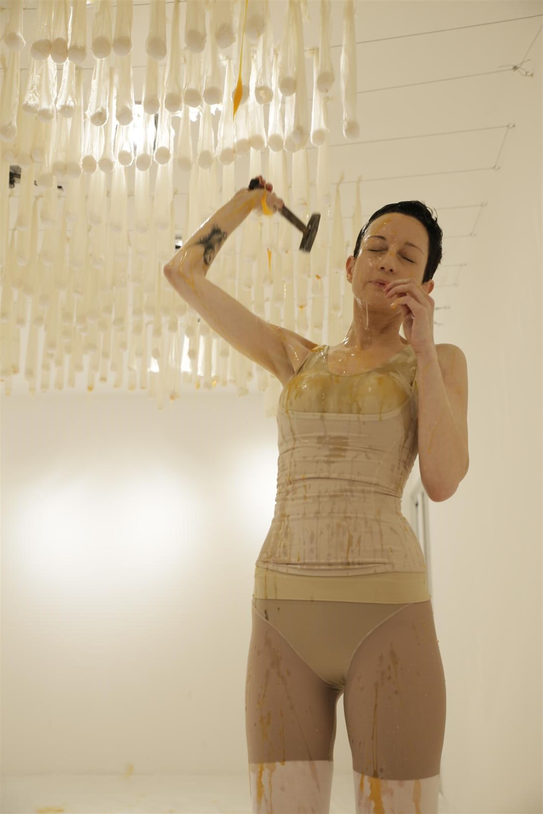 A woman in a leotard is covered with broken eggs raining down from the ceiling, which she strikes with a hammer