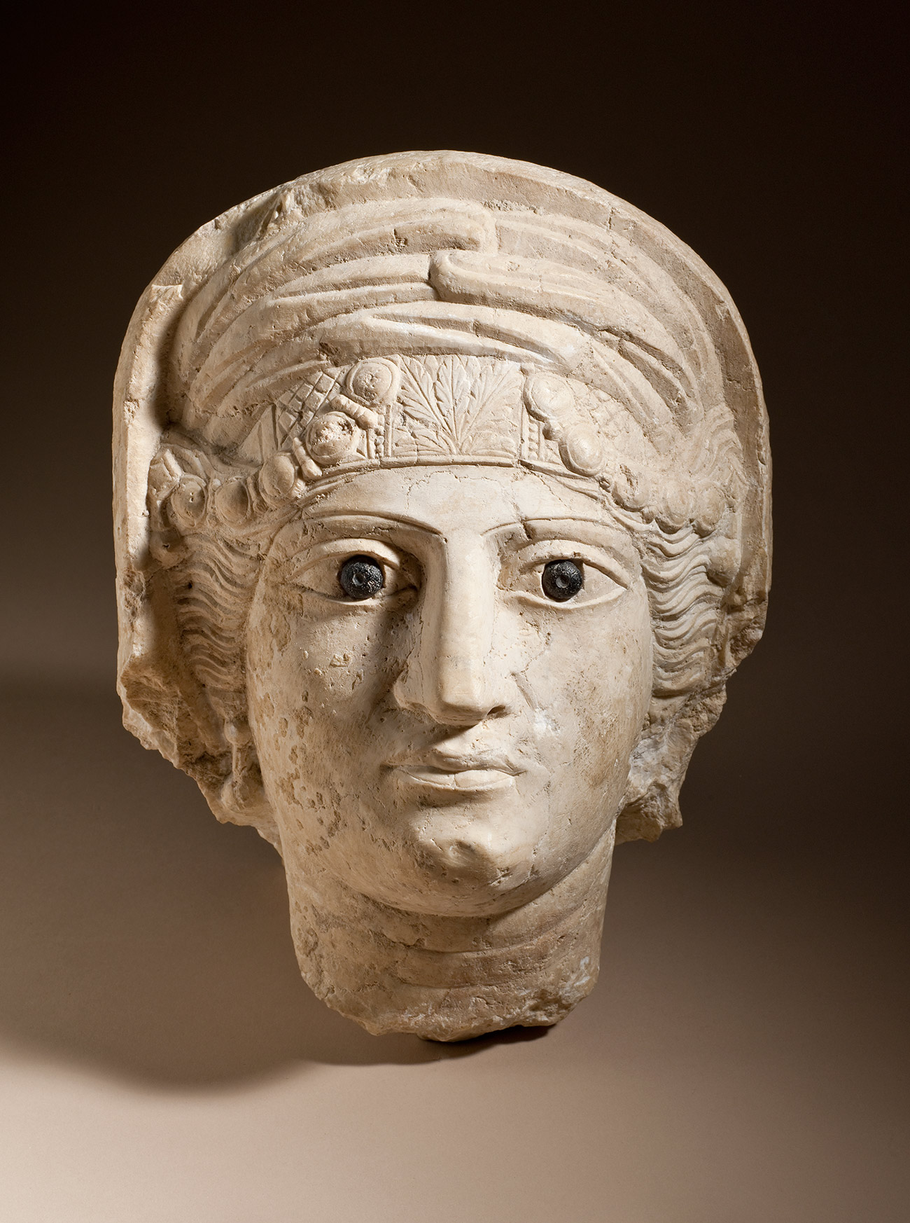 Carved limestone head of a woman with black-painted irises and ornamented headgear