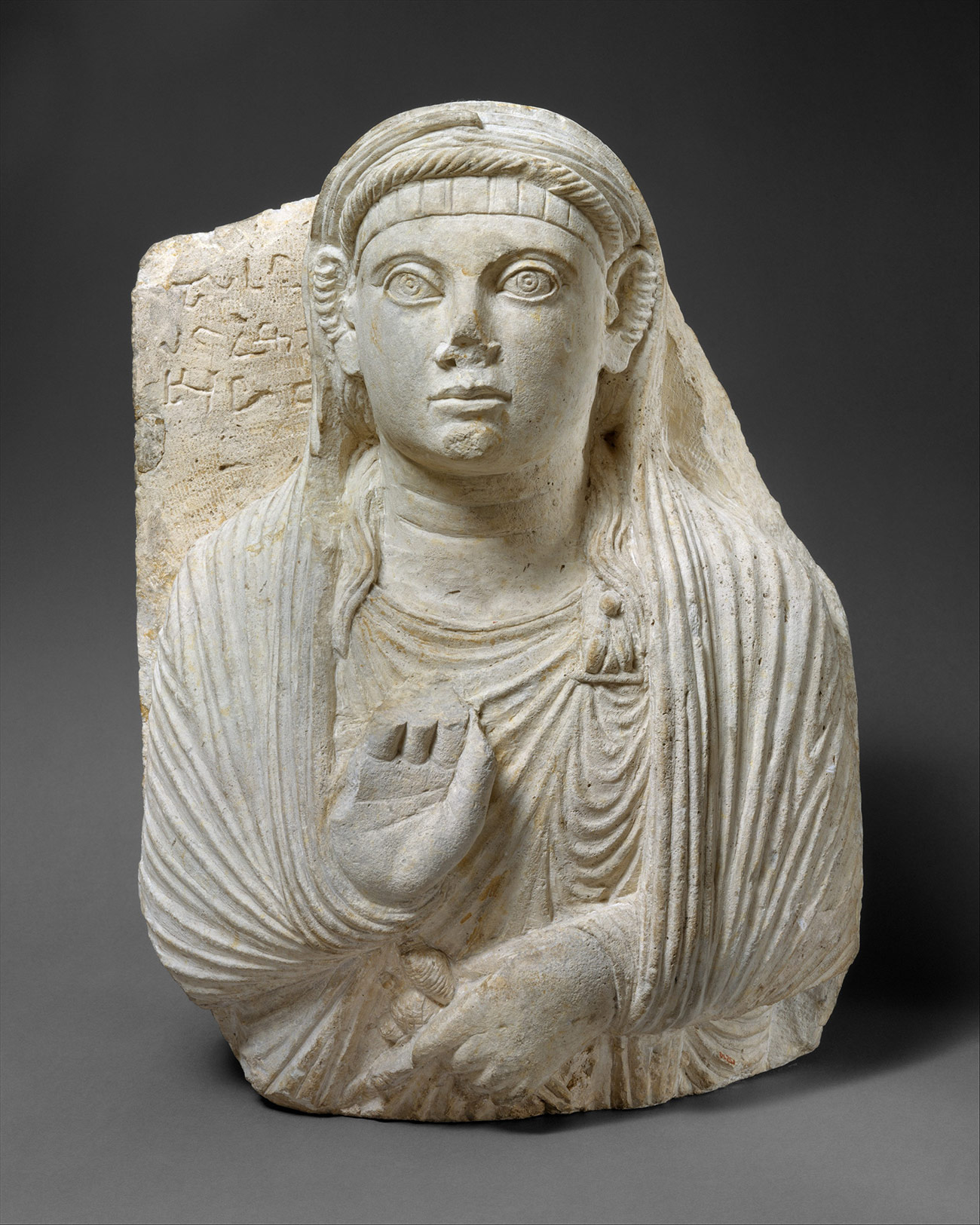 Bust of a woman dressed in a draped garment, pinned at the left shoulder with an elaborate brooch, who faces directly towards us