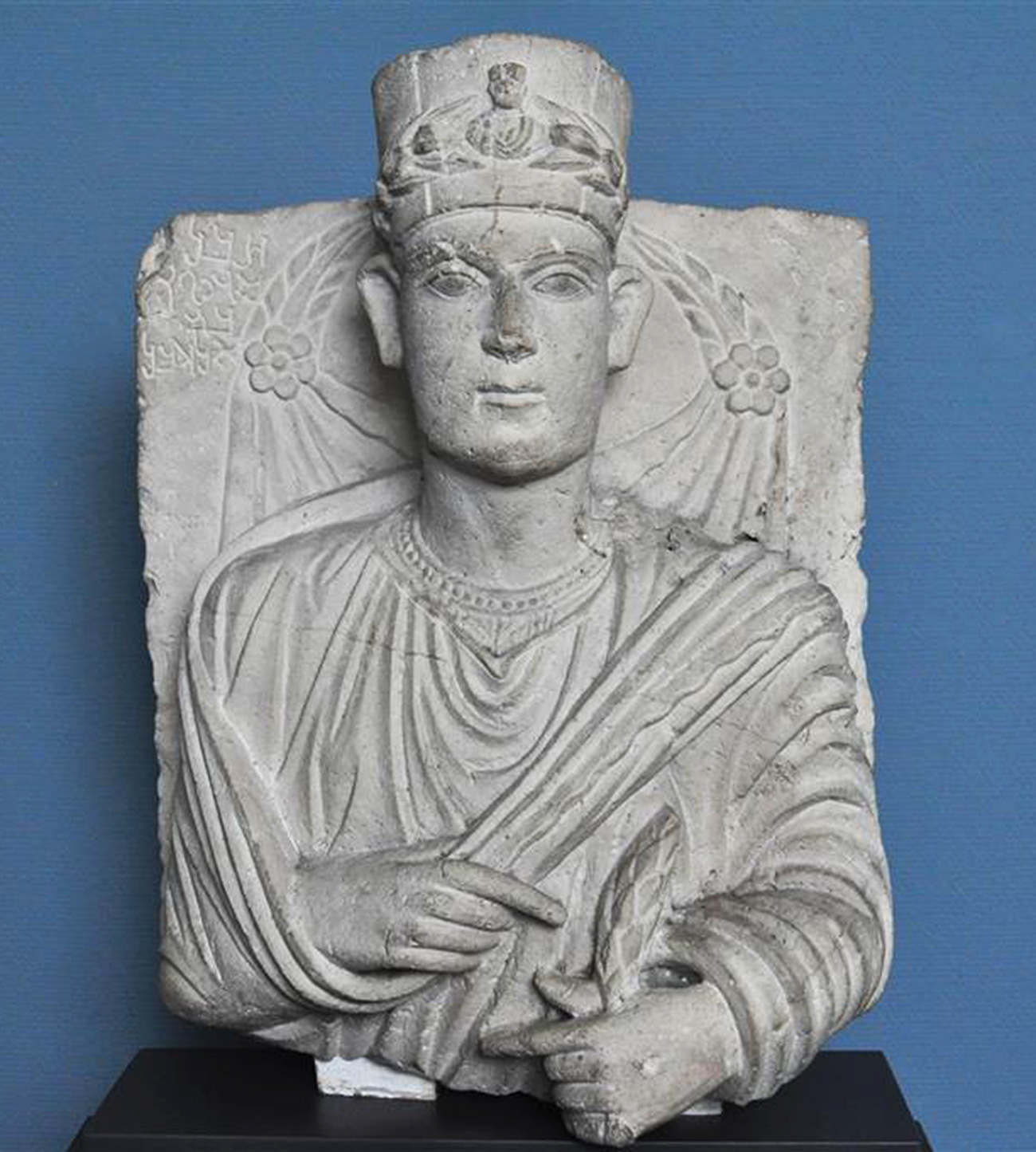 Limestone bust of an ancient Palmyrene priest wearing a tunic and ceremonial headgear
