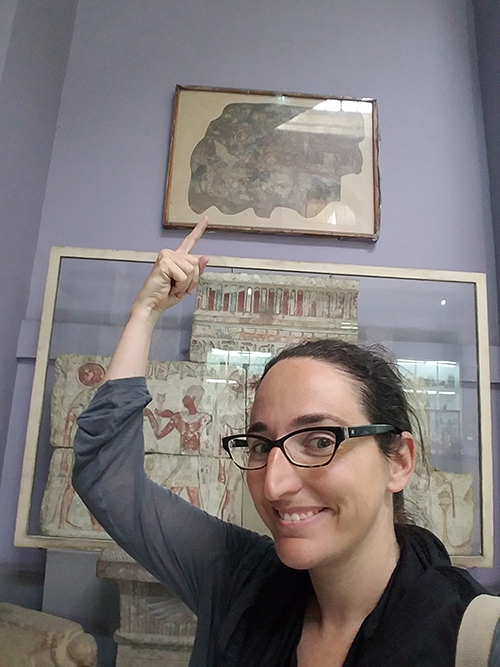 A young woman smiles and gestures to framed fresco fragments on a museum wall behind her