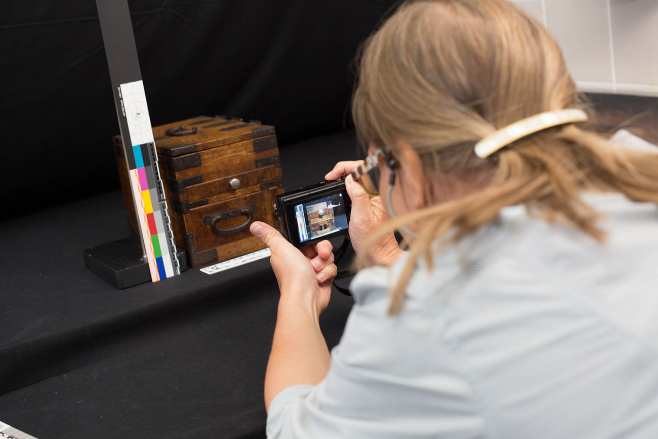 Close-up view of Foekje Boersma photographing a small wood box