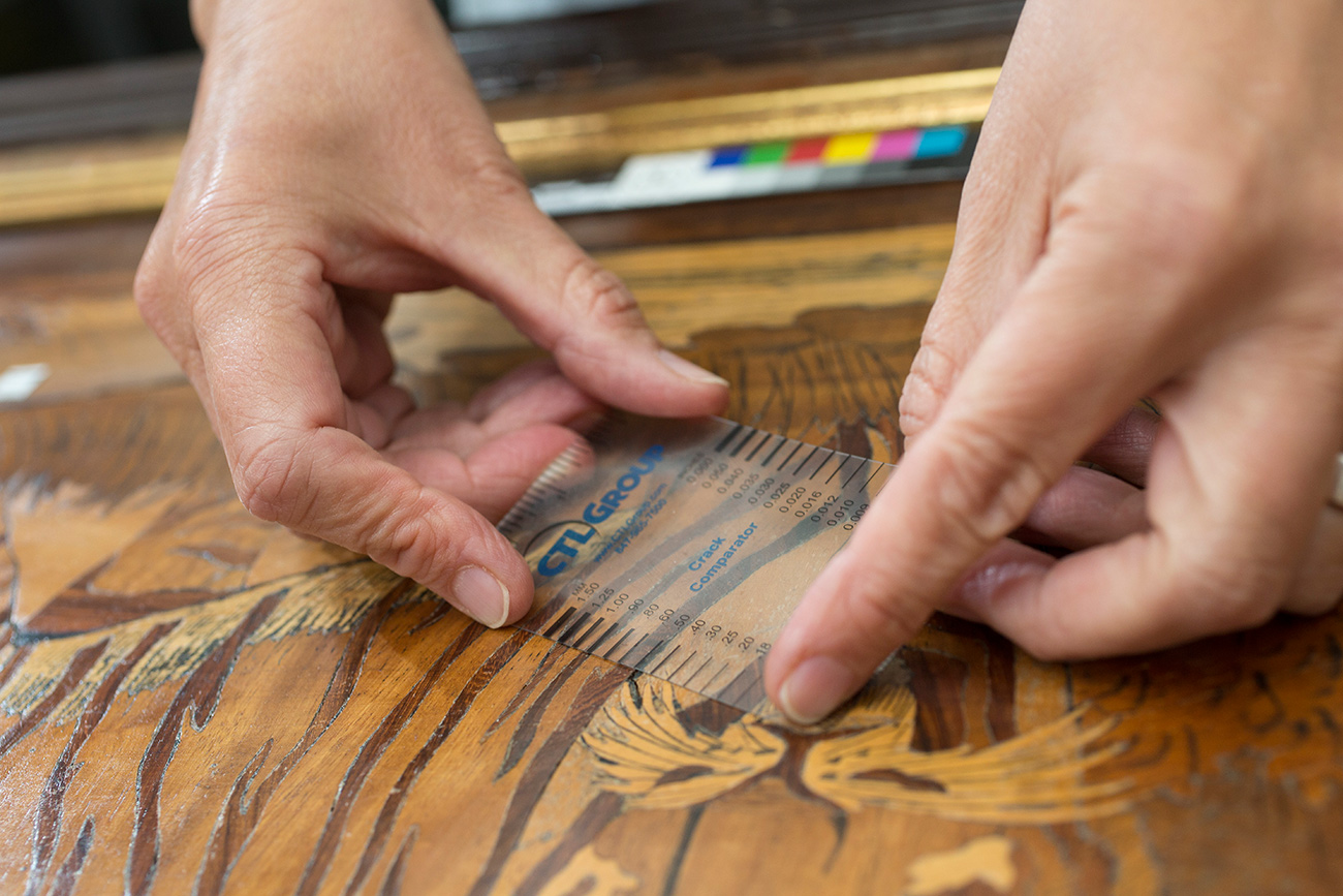 Close-up of Foekje Boersma's hands holding a translucent short ruler against the top of a wooden art object