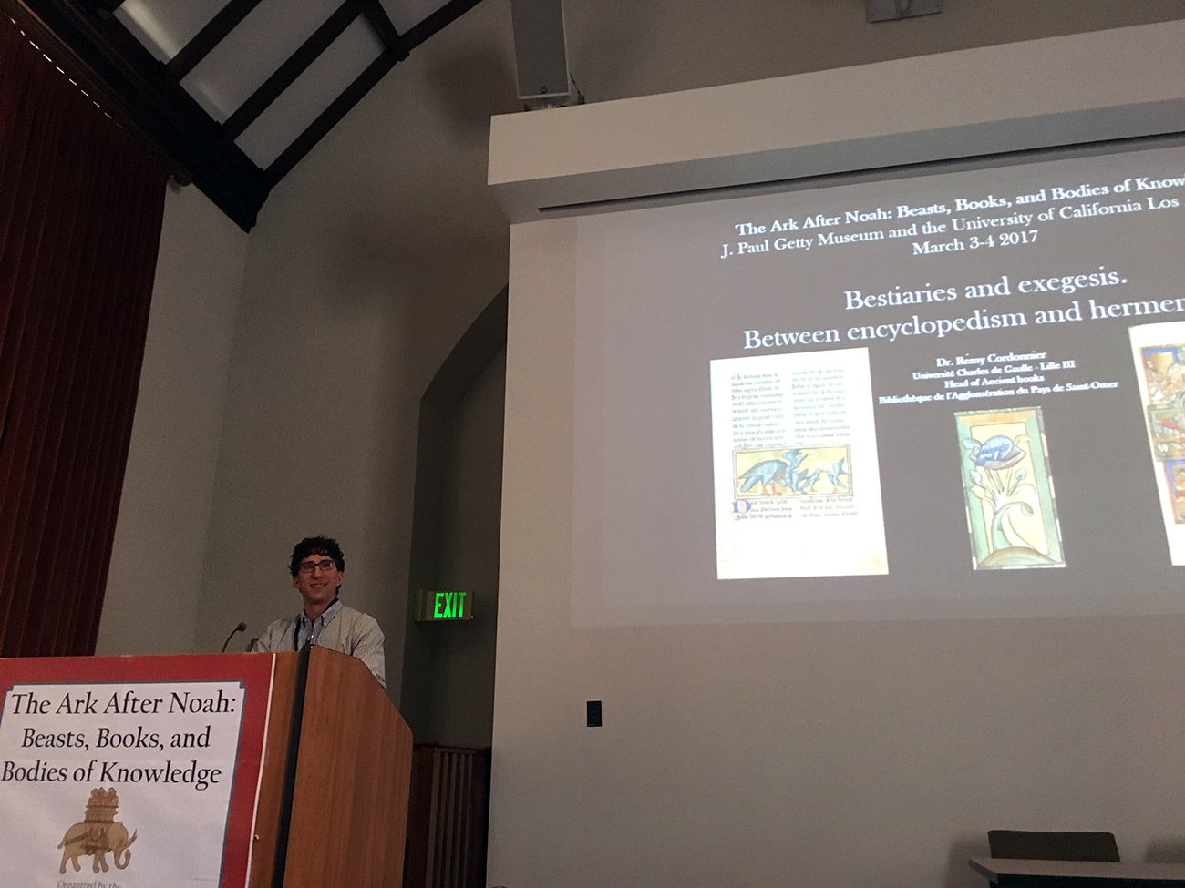 A man speaks, standing at a podium. Behind him, images of medieval illuminated bestiaries