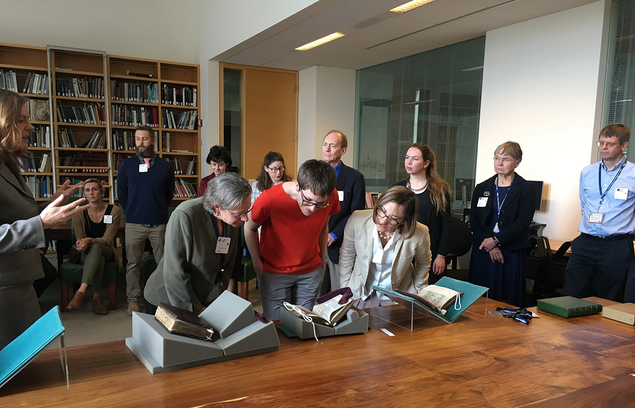 A group of scholars gather around open manuscripts displayed on a wooden table