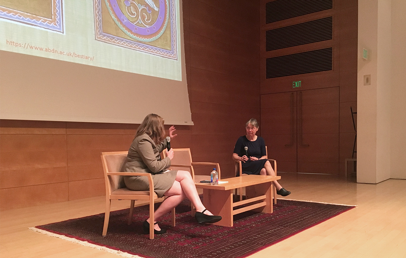 Two women, seated, speak to each other on an auditorium stage, with images of medieval manuscripts on the large screen behind them