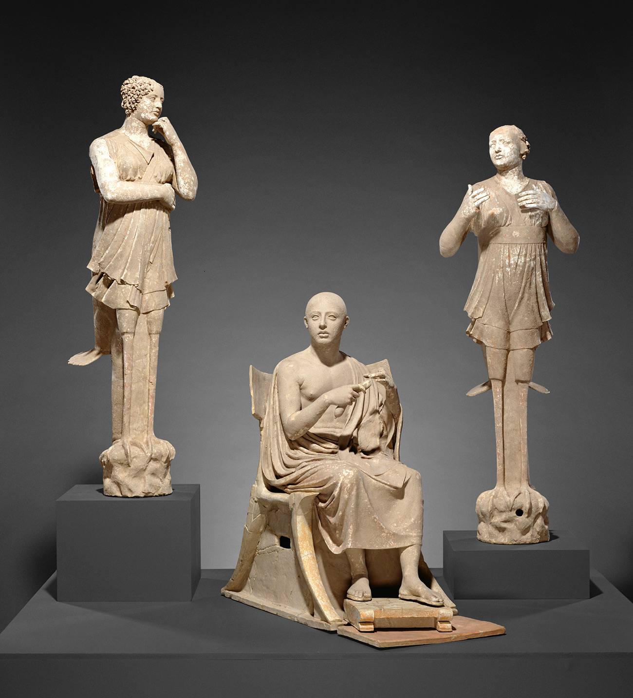 Life-size terracotta figure of a poet seated on a throne and flanked by two women with wings and the claws of birds