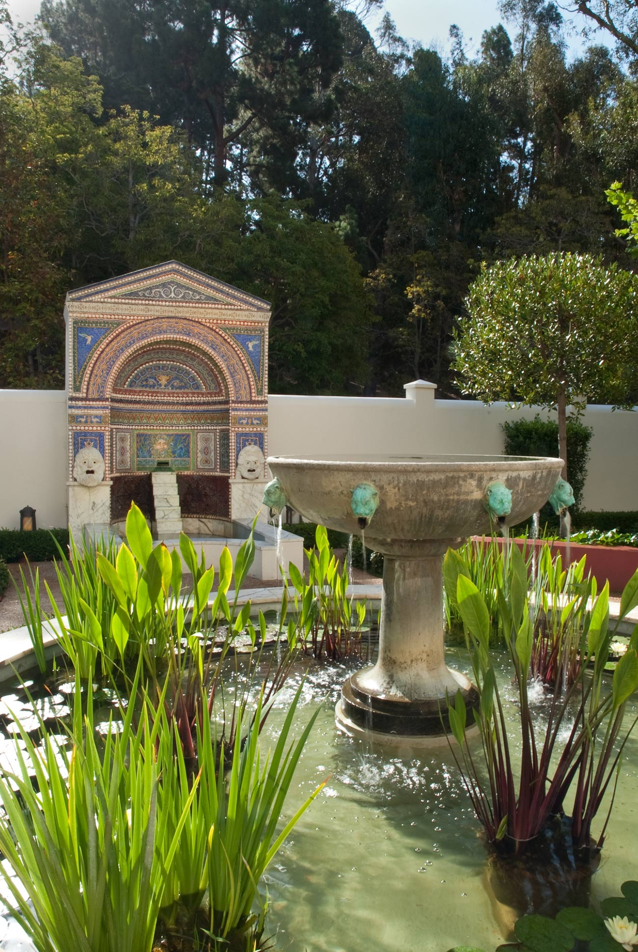 Daytime view of an enclosed garden at the Getty Villa with a central fountain with water plants and a mosaic fountain