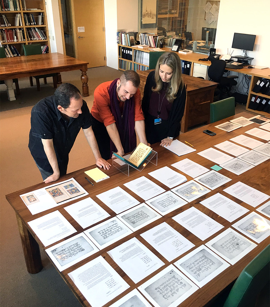 Three people examine a small illuminated manuscript with photocopies arrayed on a wooden table