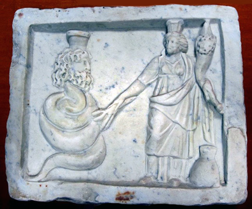 Caved marble relief showing a bearded male god with a coiled snake body and a goddess