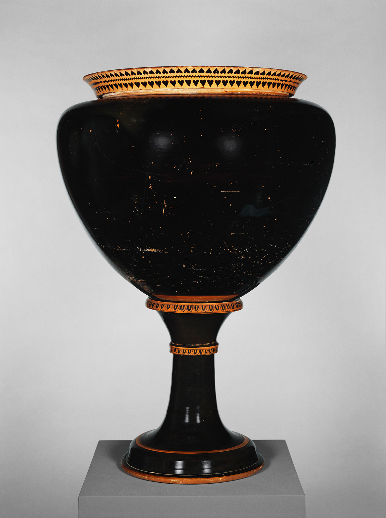 A glossy black, bulbous vase with a terracotta lip atop a tall stand