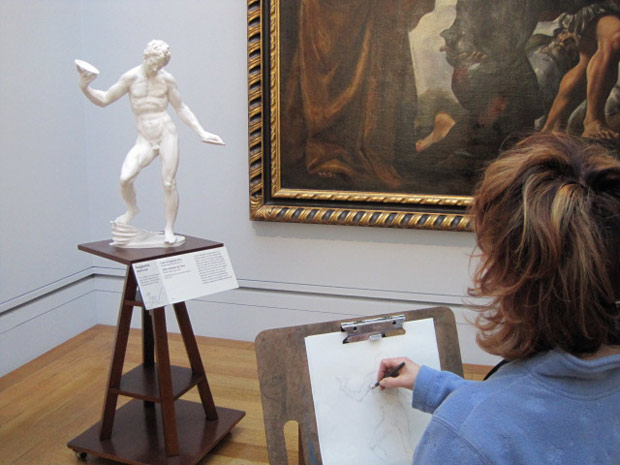 A visitor to the Sketching Gallery draws from a plaster cast of Adrien de Vries's Juggling Man.