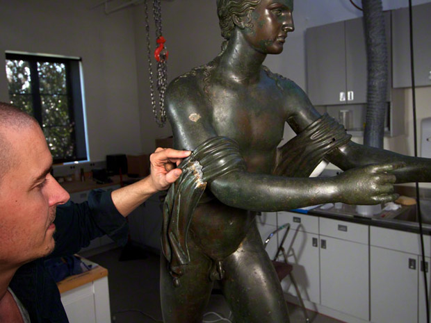 Antiquities conservator Erik Risser working on the Apollo's drapery in the Conservation Studio at the Getty Villa