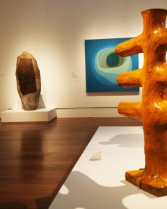 Inside Crosscurrents: Helen Lundeberg's canvas Blue Planet with John Mason's sculptures Vertical Sculpture, Spear Form and Orange Cross