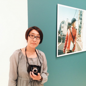 Mikiko with her camera in front of her photograph on view in In Focus: Tokyo