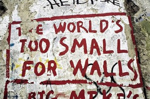 Graffiti on the Berlin Wall reading, the world's too small for walls