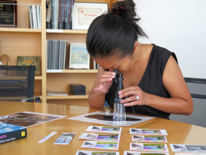Getty Conservation Institute project specialist Tram Vo examines a color photographs with a handheld loupe