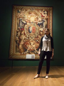 Grad intern Amelia Brown photographed in Woven Gold: Tapestries of Louis XIV. In the background is Portiere of the Chariot of Triumph / design by Charles Le Brun; woven at the Gobelins Manufactory