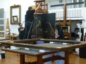 Getty art handlers place Guercino's Jacob Blessing the Sons of Joseph on an easel.